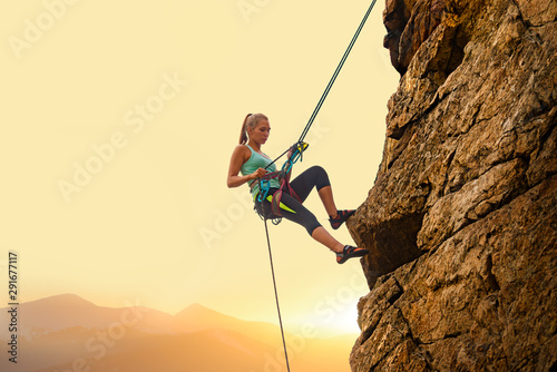 Fotomural Beautiful Woman Climbing on the Rock at Foggy Sunset in the Mountains