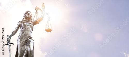 Fotomural  Justitia Statue vor einem Himmel mit den Sonnenstrahlen im Hintergrund