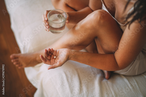 Obraz Top view of woman holding glass of water and pill - fototapety do salonu