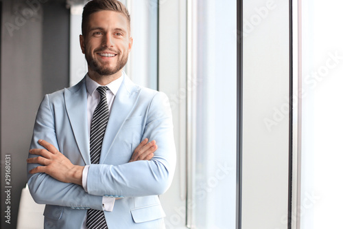 Carta da parati  Portrait of happy businessman with arms crossed standing in office