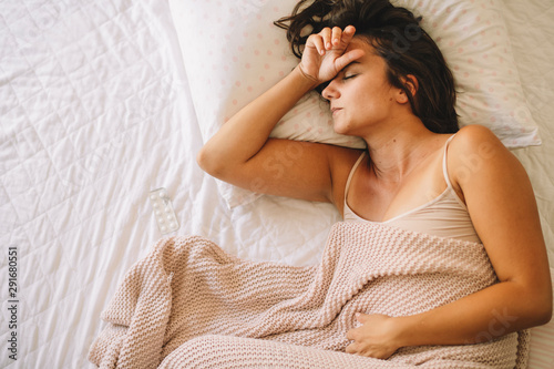 Valokuva  Young woman having stomachache lying on white bed