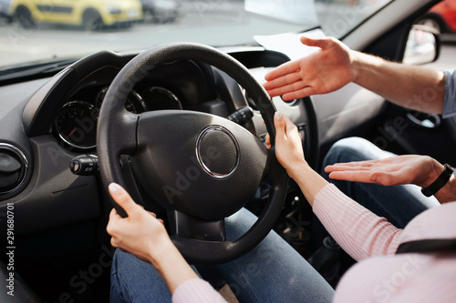 Male auto instructor takes exam in young woman. Cut view of woman's hands on steering wheel. Guy point on it and explain. Sit in car together. Exam time.