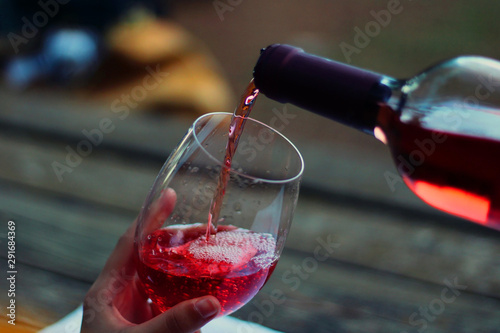 Poster Bar Young girl dressed in yellow and with hat pouring rose wine inside a wineglass.