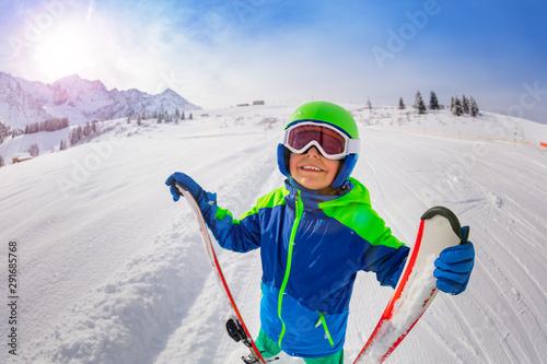 Fényképezés Happy boy on skiing slope hold ski look up smiling
