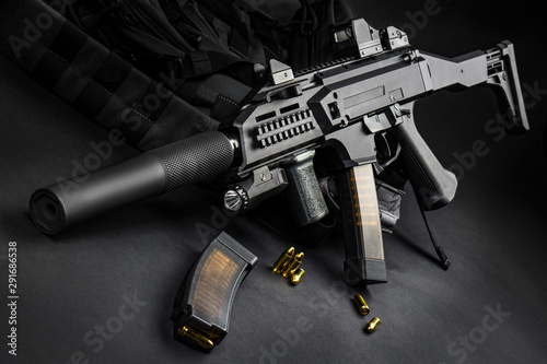 Fotomural  Modern automatic rifle with a silencer and a collimator sight on a dark background