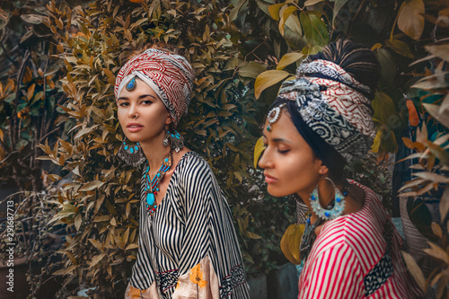 Photographie  portrait of two beautiful stylish woman wearing turban on tropical background