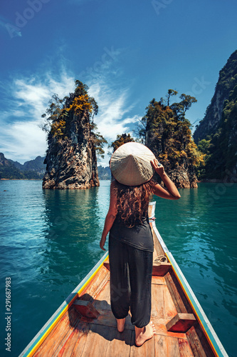 Fotografia  young woman tourist in asian hat on the boat at lake