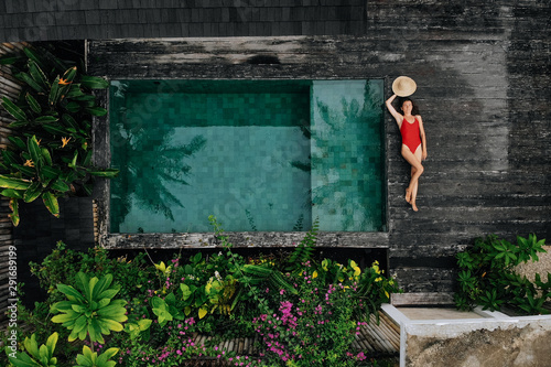 Leinwand Poster Aerial drone photo of happy Woman in red swimsuit relaxing near private pool with flowers and greenery around, Bali