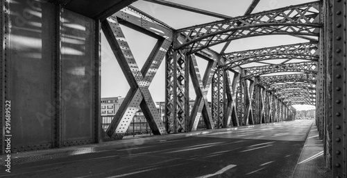 Photo sur Aluminium Ponts Black and white asphalt road under the steel construction of a bridge in the city on a sunny day. Evening urban scene with the sunbeam in the tunnel. City life, transport and traffic concept.