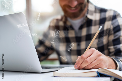 Fotografie, Obraz  Close-up on a young man's hand while he is keeping mathematical notes in his notebook holding a pencil