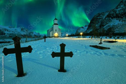 Foto auf Gartenposter Nordlicht Northern lights over winter landscape with church and graveyard