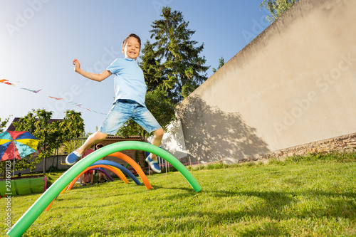 Happy boy jumps over barriers in active game