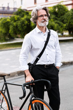 Photo Of Pleased Mature Businessman Walking With Bicycle