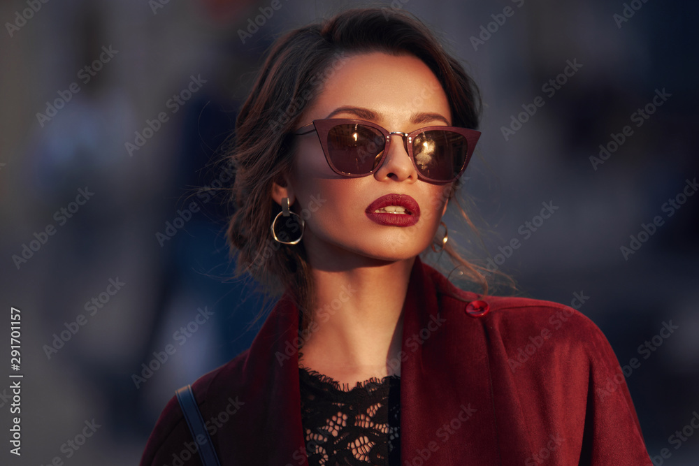 Fototapeta Closeup portrait of young elegant woman wearing sunglasses. Pretty girl with hairstyle and makeup. Outdoor portrait. Sunset light.