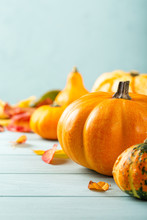Autumn Background With Yellow Leaves And Pumpkins On Blue Table. Thanksgiving And Halloween Concept With Copy Space.