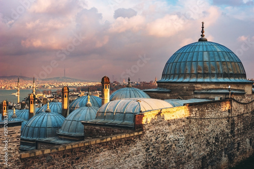 Foto auf AluDibond Cappuccino Beautiful view of the Golden Horn at sunset, Istanbul, Turkey. The roofs of the Suleymaniye Mosque in the rays of the setting sun against the blue sea in Istanbul
