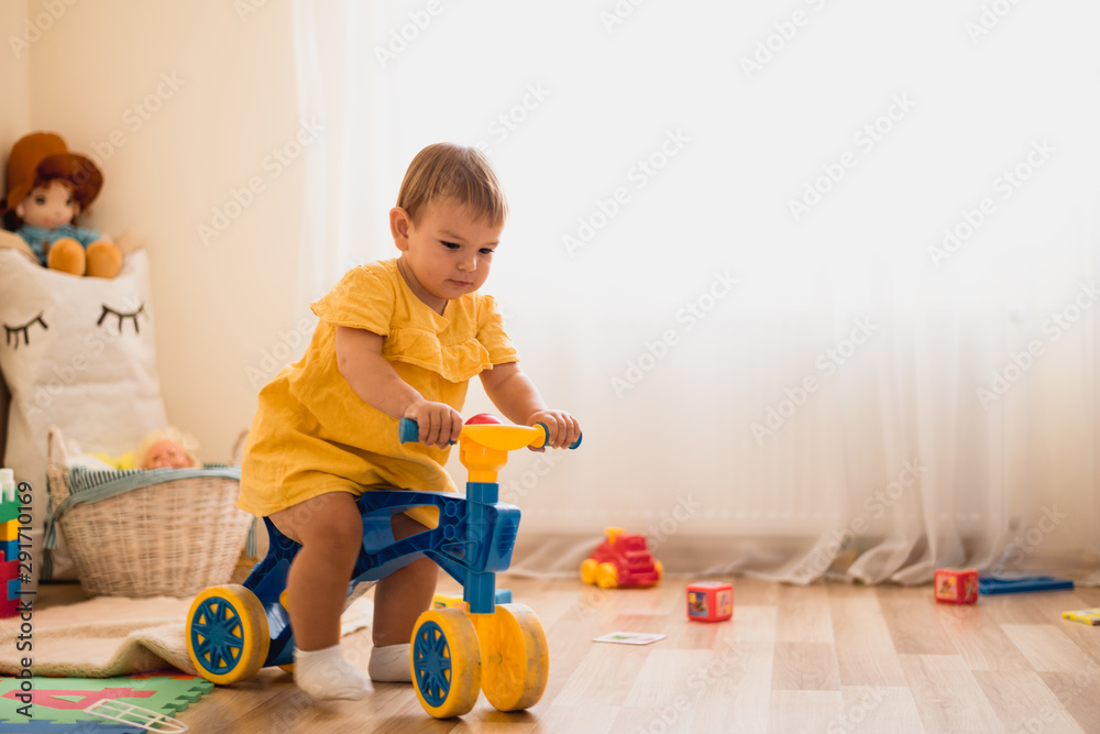 Fototapety, obrazy: Cute lovely small baby girl learning to balance on her first bike at home. Toddler activity at daycare