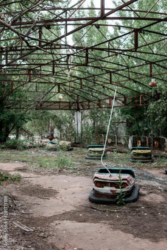 bumper cars in abandoned amusement park near trees
