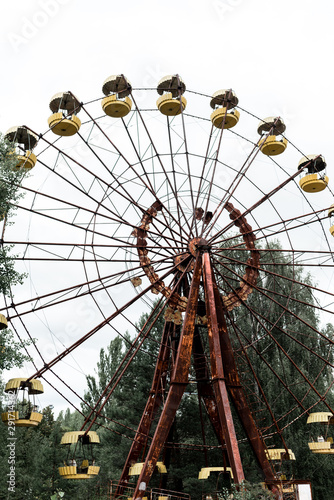 abandoned and rusty carousel in amusement park with trees against sky