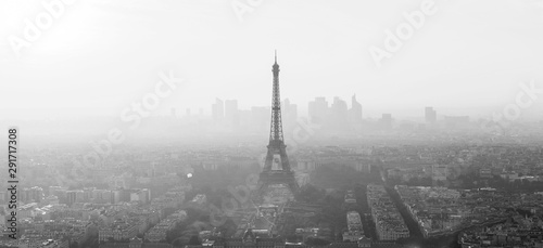 Aerial view of Paris with Eiffel tower and major business district of La Defence in background at sunset. Black and white image.