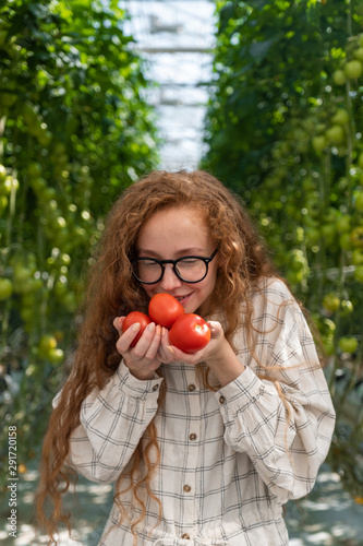 Scientist inspecting plants. Woman agronomist in greenhouse. Portrait of a Young Female Working in the Garden Center. Woman scientist Wall mural