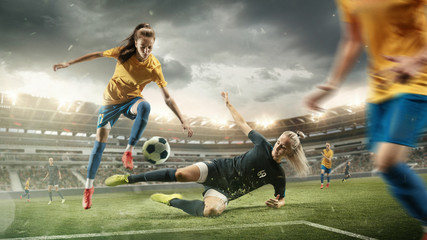 Excitement. Young female soccer or football players in sportwear kicking ball...