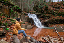 Woman Sitting On The Log Looking At Waterfall Autumn Season