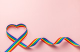 Fototapeta Tęcza - LGBT rainbow ribbon in the shape of heart. Pride symbol. Pink background. Copy space for text.