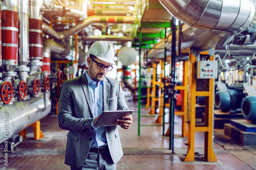 Stampa su Tela  Handsome caucasian manager in gray suit and with helmet on head using tablet while standing in power plant