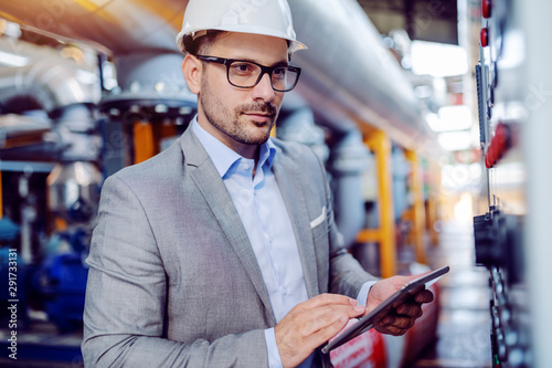 Focused handsome caucasian supervisor in suit and with helmet on head using tablet and looking at dashboard while standing in power plant Fototapeta