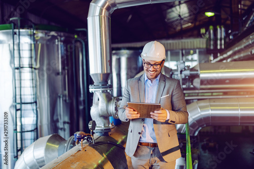 Poster Ecole de Danse Handsome smiling caucasian supervisor in suit and with helmet on head using tablet while standing in power plant.