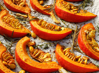 Baked Pumpkin slices with the addition of olive oil, spices and herbs on baking paper, close-up, top view. Vegan healthy food