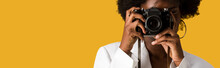 Panoramic Shot Of Curly African American Woman Covering Face While Taking Photo Isolated On Orange
