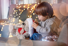 Christmas Mood. Cute Little Boy Putting Santa Red Hat On His Teddy Friend With Garland Lights Bokeh At Background At Home.  Get Ready For Miracle. Magic Of Childhood