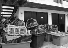 Lobster And Crab Pots Stacked Against Fishing Huts