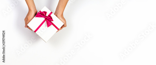 Obraz Child hands holding present gift box tied with ribbon on white background. Top view, place for text. Holiday concept - fototapety do salonu