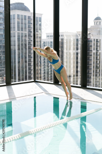 Young woman diving into indoor lap pool, high rise apartment, tall buildings in window Wall mural