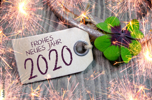 Fotografia  Wooden hang tag with four leaf clover and sparklers and with the german words fo