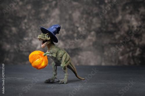 Photo  Dinosaur and halloween pumpkin on black background