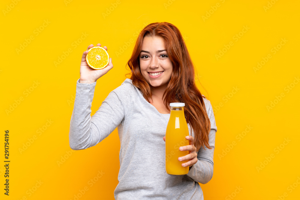 Fototapety, obrazy: Teenager redhead girl holding an orange over isolated yellow background