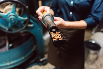 Woman taking sample of fresh beans from coffee roast machine