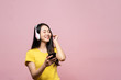 Leinwandbild Motiv Happy cheerful Asian beautiful woman wearing wireless headphones or earphone speaker listening to music from smartphone with smile. Studio shot isolated on pink background. People gesture in studio.
