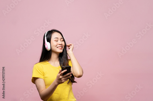 Happy cheerful Asian beautiful woman wearing wireless headphones or earphone speaker listening to music from smartphone with smile. Studio shot isolated on pink background. People gesture in studio. - 291757594