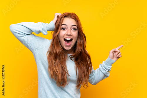 Teenager redhead girl over isolated yellow background surprised and pointing fin Slika na platnu