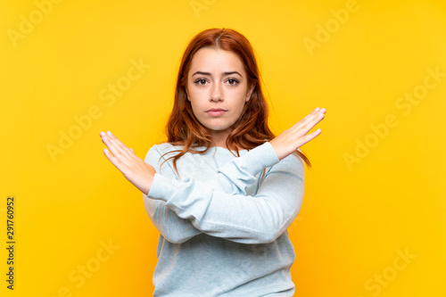 Teenager redhead girl over isolated yellow background making NO gesture Fototapet