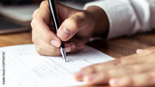 Businessman signing a document in office - fototapety na wymiar