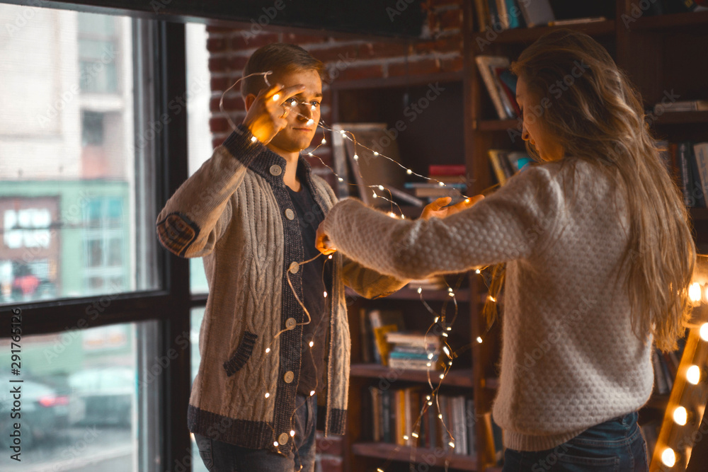 Fototapeta couple in love in a cozy room with a garland of lanterns in their hands