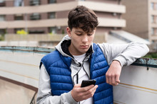 A Teenage Boy Looking Into A Phone With A Sad Face And Having Negative Emotions Because He Read The Bad News