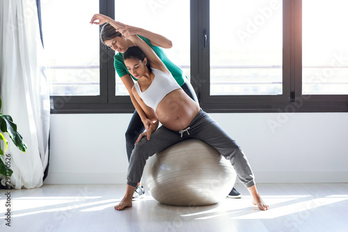 Physiotherapist helping to beautiful pregnant woman for doing pilates exercises with ball preparing for childbirth Obraz na płótnie