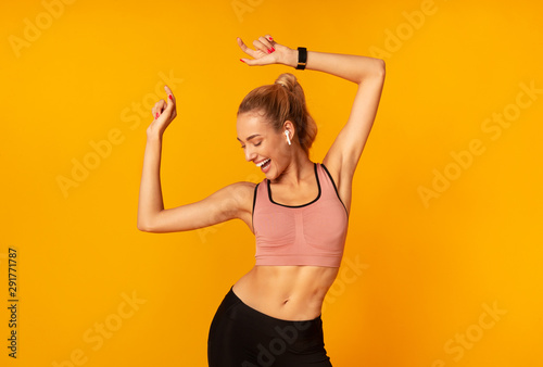 Fotografia  Woman In Wireless Earphones Dancing Listening To Music, Yellow Background